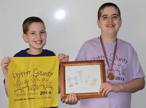 <p>Carson Powers (on right) is wearing his honorary Special Olympics medal and holding the framed photo presented to him at a special school assembly last week. He is joined by his brother, Reed, who is holding the banner presented to Carson.</p><div> </div>