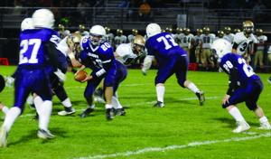 <p>Quarterback Aaron Wolfinger (20) takes the snap Friday night against Curwensville. Chase Whitman (27) is the man in motion and Brock Wilson (28) is the running back. Coudersport used a two quarterback system with Wolfinger and Jared Green splitting time under center.</p><div> </div>