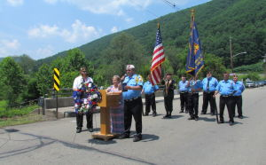 <p>Linda Cox, the wife of Douglas is behind the podium; to her left is Jesse Olson, commander of the Raymond Richar VFW Post 6611, and to her right is Don Skutski. Members of the Potter County Honor Guard presenting the American flag and the Pennsylvania flag are standing behind them.</p>