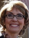 Giffords, back at tragic site, asks for wider gun checks