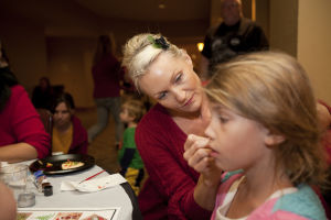 Hilton El Conquistador Tree Lighting Ceremony: Carin Nelson, who is with the Hilton's Kids Corner, paints the face of Elizabeth Mitchell, 8, during the festivities held at the resort last week. - Randy Metcalf/The Explorer
