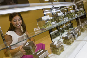 Catalina Hills Care: Catalina Hills Care's dispensary manager Ana Helber replaces a container of Granddaddy Purple medicinal marijuana back into the display case after serving a patient's order. The Oro Valley marijuana dispensary opened last week. - Randy Metcalf/The Explorer