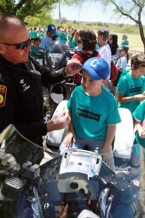 Drug Awareness Day: Oro Valley police officer Greg Burgess lets Copper Creek Elementary School's Hunter Walden know hats aren't allowed on his motorcycle by taking his hat off.  - Randy Metcalf/The Explorer