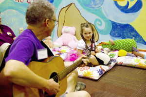 Tu Nidito: Bruce Phillips, music specialist at Tu Nidito, plays the guitar as Presley Gyuro looks on. Tu Nidito is a non-profit organization that helps families that have a seriously ill child, seriously ill parent, or are grieving the death of a loved one. - Hannah McLeod/The Explorer