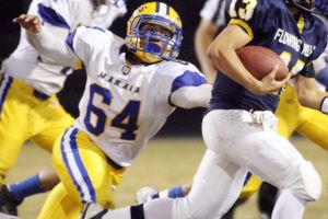 Marana Vs Flowing Wells Football: Marana senior Caleb Stewart tries to wrap up the Flowing Wells quarterback in the backfield. - Randy Metcalf/The Explorer
