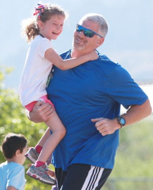 Painted Sky Elementary School's Miler's Club: Craig Collings runs while carrying his 5-year-old daughter Micaela.  - Randy Metcalf/The Explorer