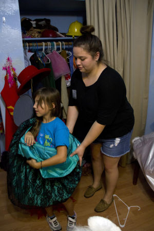 Tu Nidito: Volunteer Monica Montes helps a Jalyn Friend put on a dress as she plays dress-up with other girls. - Hannah McLeod/The Explorer