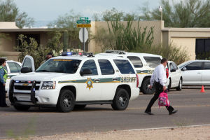 Suspect Stopped Along Shannon Road: A man with the Pima County Sheriff's Office carries a child's backpack from the scene where deputies were able to force a vehicle off the road. The driver, who had his 4-year-old child in the car, refused to stop went deputies tried to stop him. - Randy Metcalf/The Explorer
