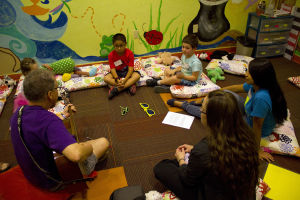 Tu Nidito: The little group, ages 3 1/2-7, listen to Bruce Phillips play the guitar. - Hannah McLeod/The Explorer