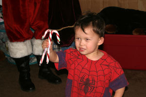 Give To Win A Success For Families: Caleb, 2, gets candy canes for his sister and dad from Santa. - Thelma Grimes/The Explorer