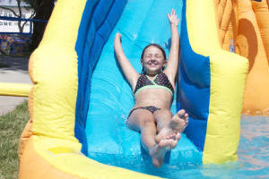 Amphibious Athletes: Anna Daines raises her hands as she slides down the water slide at the Amphibious Athletes Land and Water Activity Program. The program consists of week-long camps that give children a variety of water and land activities.  - Hannah McLeod/The Explorer