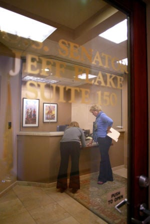 Protesting U.S. Sen. Jeff Flake: Melissa Martin, a constituent services representative with U.S. Sen. Jeff Flake, left, takes a petition with nearly 70 signatures from Johnna Matthews.  - Randy Metcalf/The Explorer