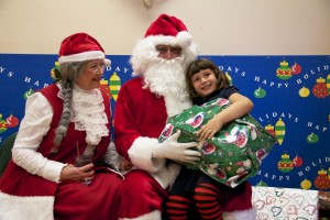 Elks Lodge Helps Start Off Christmas Right: Santa Claus and Mrs. Clause give a young girl a gift and take a picture with her.  - Hannah McLeod/The Explorer