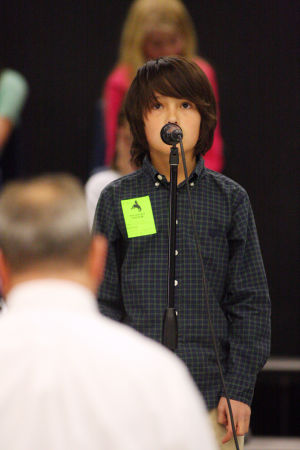 Amphitheater School District Spelling Bee: Mesa Verde Elementary School student Kyle Newlin spells out his word during the Amphitheater School District's spelling bee.  - Randy Metcalf/The Explorer