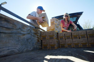Girl Scout Cookies: Keith Boesen and Jessica Galow load a trailer with 2,700 boxes of Girl Scout cookies last week at Casas Church for Troop 347. - Randy Metcalf/The Explorer
