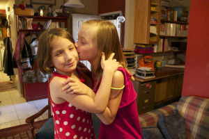 Russia Adoption: Libby kisses younger sister Abby on the cheek. - Hannah McLeod/The Explorer