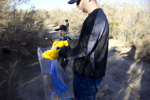 Xpress Baseball: Bubba Mustain drops trash into a bag held by Coach Brian Hooten. The Xpress Baseball team is a non-profit club that consists of 50 players. - Hannah McLeod/The Explorer