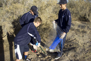 Xpress Baseball: Julian DeAlva (left), Brady Arffa and Levi White (right) help clean the Canada Del Oro Wash that runs under East Pusch View Lane. - Hannah McLeod/The Explorer