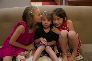 Russia Adoption: Libby (right) and Abby (left) show affection to their younger brother Gideon. - Hannah McLeod/The Explorer