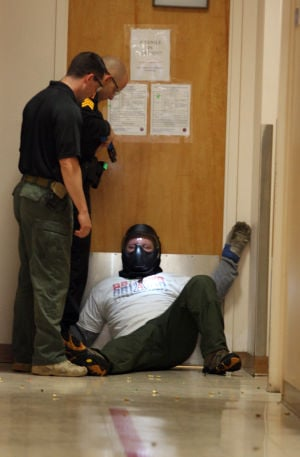 Active Shooter Training: During a training exercise demonstration, Officer Mike Gracie, left, and Sgt. Zach Pierce stand over Officer Anthony Castiglia, who played the role of an active shooter. Simulation ammunition, which fired paint pellets, was used in the exercise to check the officer's aim. - Randy Metcalf/The Explorer