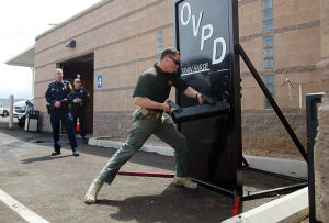 Active Shooter Training: Officer Mike Gracie demonstrates how to breach open a door using a battering ram. - Randy Metcalf/The Explorer