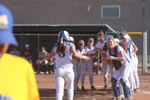 Marana Vs Desert Ridge Softball: MaranaÕs Sierra Cuestas gets a welcome at home plate after hitting one over the fence during last weekÕs playoff game.  - Randy Metcalf/The Explorer