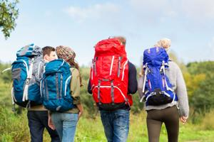 adventure, travel, tourism, hike and people concept - group of friends walking with backpacks from b