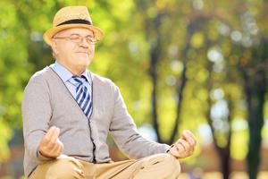 Senior gentleman meditating seated on a green grass in a park during autumn