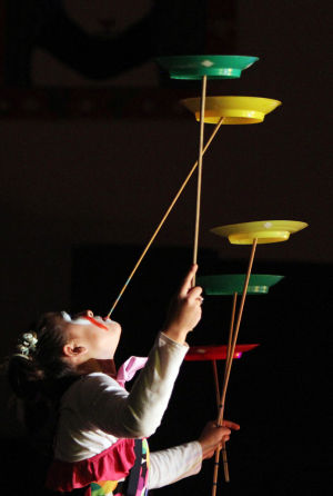 Clown College: Candace Contreras manages to balance five spinning plants on sticks, using both her hands and her mouth. Earlier this month, students at Wilson K-8 put on a circus show as part of its clown college portion of class. - Randy Metcalf/The Explorer
