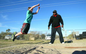 Olympic Medalist Michael Bates: Michael Bates watches as Mesa Verde Elementary School fifth-grader Clay Haskins practices the long jump.  - Randy Metcalf/The Explorer