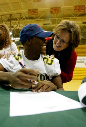 NW Students Sign Letters-of-intent 1: Canyon Del Oro Principal Marcia Volpe congratulates Ka'Deem Carey on signing with the University of Arizona. Carey's mother learned of her son's decision when she pulled a UA hat from a box.  - Randy Metcalf/The Explorer