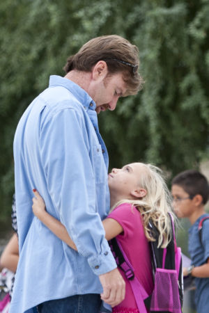 First Day Of School At Twin Peak Elementary School: Chris Neely gets a hug from his daughter Sierra, who was starting the third grade, as they wait for the gates at Twin Peaks Elementary School to open. - Randy Metcalf/The Explorer