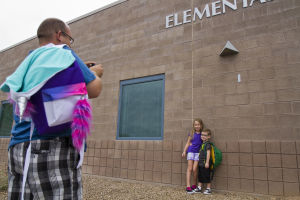 First Day Of School At Twin Peak Elementary School: Kevin Trimble takes a photo of his son Dyllan and Janae in front of the school's façade, which has the Twin Peaks Elementary School sign. - Randy Metcalf/The Explorer
