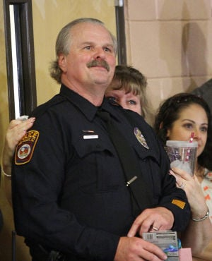 Oro Valley Police Officer Ed Holdinsky: Oro Valley Police Officer Ed Holdinsky and his wife, Rita, watch a slide show depicting his time at Copper Creek Elementary School as a Student Resource Officer. - Randy Metcalf/The Explorer