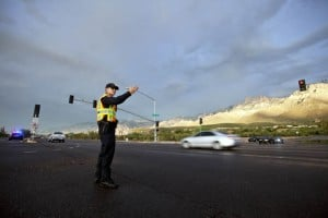 Monsoons: Oro Valley Police Officer Zach Young directs traffic at Oracle Road and First Avenue due to the traffic light malfunctioning after the storm Sunday evening. - J.D. Fitzgerald/Special to the Explorer