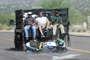 Motorcycle Accident Class: Consultant Todd Frank, left, Northwestern University Instructor Mike DiTallo, middle, and Oro Valley motor officer Jeff Thomas push a motorcycle off the back of a moving truck during a motorcycle accident reconstruction class last week. For more photographs, go to explorernews.com. - Randy Metcalf/The Explorer