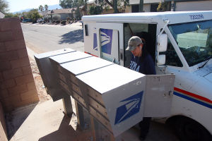 United States Postal Service: Carolina Estrada, who is a rural carrier for the United States Postal Service, delivers the mail last week. Beginning in August, the USPS will end standard mail deliveries on Saturdays.  - Randy Metcalf/The Explorer