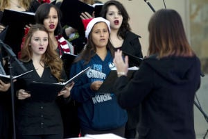 Marana Christmas: Jennifer Delagarza (left) and Taya Delgado (right) of Voices Unlimited from Mountain View High School follow the instructor's lead. - Hannah McLeod/The Explorer