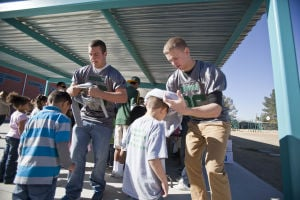 Canyon Del Oro Football Team's Hoodie Drive: Canyon Del Oro junior Thomas Sawyer, right, helps Vesary Landin with his need hoodie, as CDO junior Joshua Cronk helps Destry Benally during the annual hoodie donation at Prince Elementary School. - Randy Metcalf/The Explorer