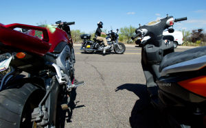 Motorcycle Accident Class: Oro Valley police officer Brian Kleinberg rides his bike past motorcycles that were later thrown off the back of a truck during a motorcycle accident reconstruction class. - Randy Metcalf/The Explorer