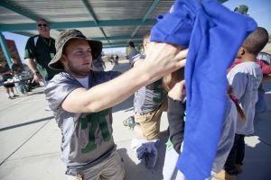 Canyon Del Oro Football Team's Hoodie Drive: Dorado junior Austin See helps a kindergartner at Prince Elementary School put on a sweatshirt last week. - Randy Metcalf/The Explorer