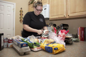 Kathy Bullerman: Kathy Bullerman prepares one of her many meals that she cooks for her clients.  - Hannah McLeod/The Explorer