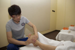 AZ Massage Center: Guang Li (Andy) rubs cream on the foot of co-worker, Yan Sailer, as he demonstrates one of the first steps of giving a foot massage. AZ Massage Center opened beginning of April and offers reflexology foot massages, hot stone massages, aromatherapy and personalized massage treatments.  - Hannah McLeod/The Explorer