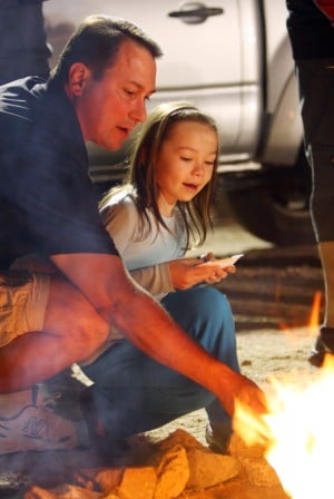 Oro Valley Holiday Tree Lighting: Mike Grabill and his 6-year-old daughter Madeline roast a marshmallow for smores.  - Randy Metcalf/The Explorer