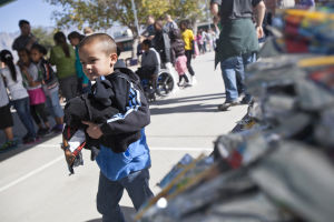 Canyon Del Oro Football Team's Hoodie Drive: After getting his hoodie and a Caprice Sun, kindergartner Jordon Foster heads to get a free ice cream sandwich at Prince Elementary School last week. - Randy Metcalf/The Explorer
