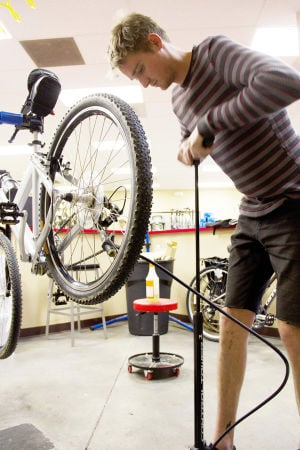 BR Bicycle Ranch: Employer, Jared Thompson, pumps up a bike tire. - Hannah McLeod/The Explorer