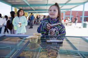 Canyon Del Oro Football Team's Hoodie Drive: Third-grader Hayli LaRose picks up an ice cream sandwich after getting a hoodie from the Canyon Del Oro football team's hoodie drive. - Randy Metcalf/The Explorer