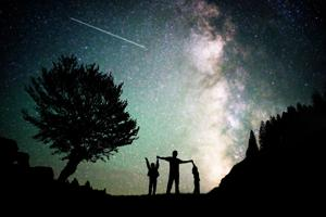 Happy family father and boys silhouette with Milky Way and beautiful night sky full of stars in back