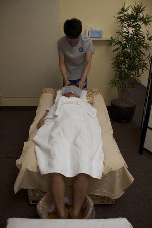 AZ Massage Center: Guang Li (Andy) massages the head of co-worker Yan Sailer in a demonstration.  - Hannah McLeod/The Explorer