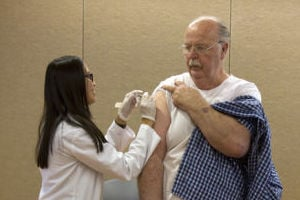 Flu Shot: Jill Ruth Nyugen, from CVS pharmacy, administers a flu shot to 66-year-old Allen Schindler. - Hannah McLeod/The Explorer